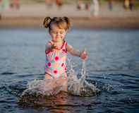 Baby girl playing with a water in the sea Stock Photo