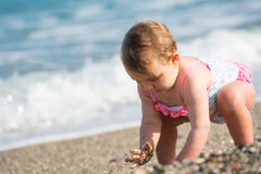 Baby girl playing in waves Stock Images