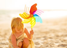 Baby girl playing with windmill toy on beach Royalty Free Stock Image