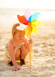 Baby girl playing with windmill toy on beach Stock Image