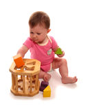 Baby girl playing with wooden shape sorter. Cutout Stock Photo