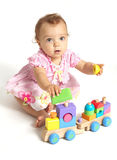Baby girl playing with an wooden train toy Stock Images
