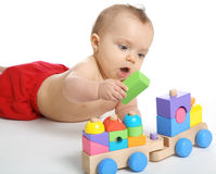 Baby girl playing with an wooden train toy Stock Image