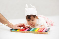 Baby girl playing with xylophone on blanket at home Stock Image