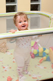 Baby girl in playpen. Happy baby girl in playpen with toys Royalty Free Stock Image