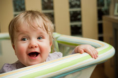 Baby girl in playpen. Cute baby girl stand in playpen, with a cheerful open smile Stock Photography