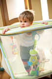 Baby girl in playpen. Cute baby girl stand in playpen, living room with backlight Royalty Free Stock Images