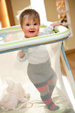 Baby girl in playpen. Cute baby girl stand in playpen, living room with backlight Stock Image