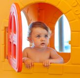 Baby girl plays at the beach in a miniature house Royalty Free Stock Image