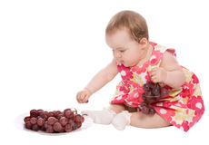 Baby girl plays with grapes Royalty Free Stock Photos