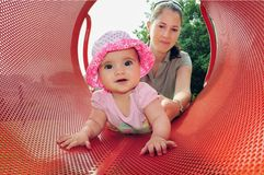 Baby Girl Plays with Mum in Playground. A little six month old baby girl plays with her mom in a playground Royalty Free Stock Photography
