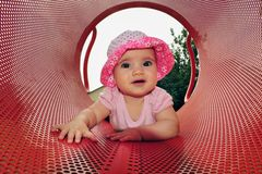 Baby Girl Plays in Playground. A little six month old baby girl plays in a playground Royalty Free Stock Images