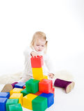 Baby girl plays with toy blocks Stock Photo