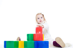 Baby girl plays with toy blocks Stock Photos