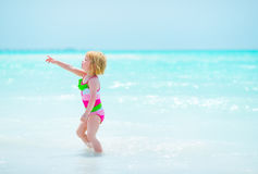 Baby girl pointing on copy space on sea coast Stock Photo