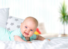 Baby girl portrait empty space background. Infant lying on bed indoors.Healthcare lifestyle concept.Caucasian happy newborn stock photography