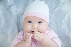 Baby girl portrait with hand in mouth lying on bed Stock Photos