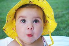 Baby girl portrait. Smiling, happy, cute and irresistible baby face with brown eyes and hair and yellow hat close up view royalty free stock photo