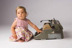 Baby Girl Posing with Typewriter Royalty Free Stock Photos