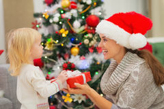 Baby girl presenting mother Christmas gift Stock Photos