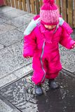 Baby girl puddle pink winter clothes boots female Royalty Free Stock Image