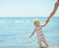Baby girl pulling mother in sea Royalty Free Stock Photos