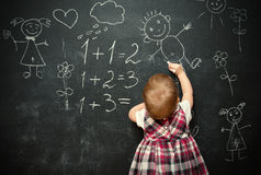 Baby girl pupil draws a chalk on blackboard Royalty Free Stock Photography