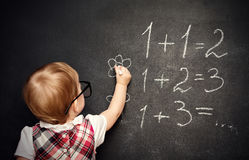 Baby girl pupil draws a chalk on blackboard Stock Image