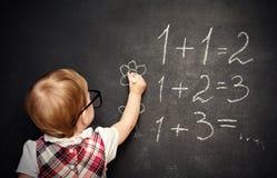 Baby girl pupil draws a chalk on blackboard. Baby girl pupil draws a chalk on a blackboard Stock Image