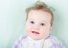 Baby girl in a purple dress lying on a green knitted blanket Royalty Free Stock Photos