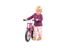 Baby girl pushing a small bike Stock Images