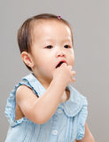 Baby girl put finger into mouth Royalty Free Stock Photo