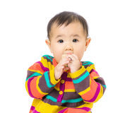 Baby girl put toy block into mouth Stock Photo