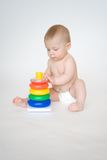 Baby girl with pyramid toy Stock Images