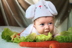 Baby girl in a rabbit hat laying among veggies. Baby girl in a rabbit hat laying on her tummy among cabbage leaves and carrots. She is looking curiously to her royalty free stock photography