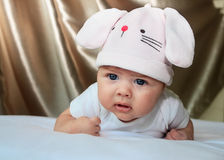 Baby girl in a rabbit hat. 2,5 month baby girl in a rabbit hat laying on her tummy. She looks concentrated as now able to hold her head for longer time. She is royalty free stock photo