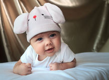 Baby girl in a rabbit hat. 2,5 month baby girl in a rabbit hat laying on her tummy. She looks happy as now able to hold her head for longer time. She is looks Royalty Free Stock Image