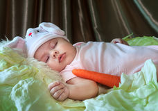 Baby girl in a rabbit hat sleeping among cabbage leaves. Stock Image