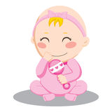 Baby Girl Rattle. Little baby girl holding and shaking a pink rattle and smiling happily Royalty Free Stock Photo