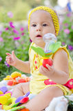 Baby girl with a rattle. Baby girl sitting in a park with a rattle in her hand royalty free stock photo