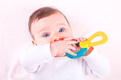 Baby girl with rattle teether toy. Royalty Free Stock Photography