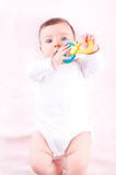 Baby girl with rattle teether toy. Stock Image