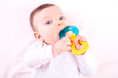 Baby girl with rattle teether toy. Royalty Free Stock Images