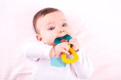 Baby girl with rattle teether toy. Image of baby girl with rattle teether toy royalty free stock images