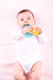 Baby girl with rattle teether toy. Stock Photography