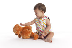 Baby girl reaching for her toy bear Stock Images
