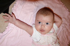 Baby girl reaching out her arm. Baby girl stretching out her arm with a serious look on her face Stock Photography