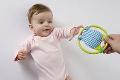 Baby girl reaching for toy Royalty Free Stock Photo