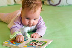 Baby girl reading. Cute baby girl reading a book on bed Stock Photo