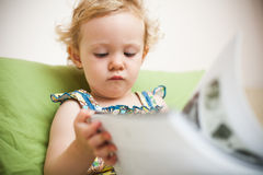 Baby girl reading Royalty Free Stock Photos